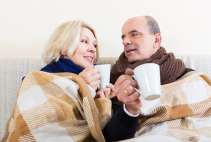 Mature loving spouses under blanket drinking tea on couch